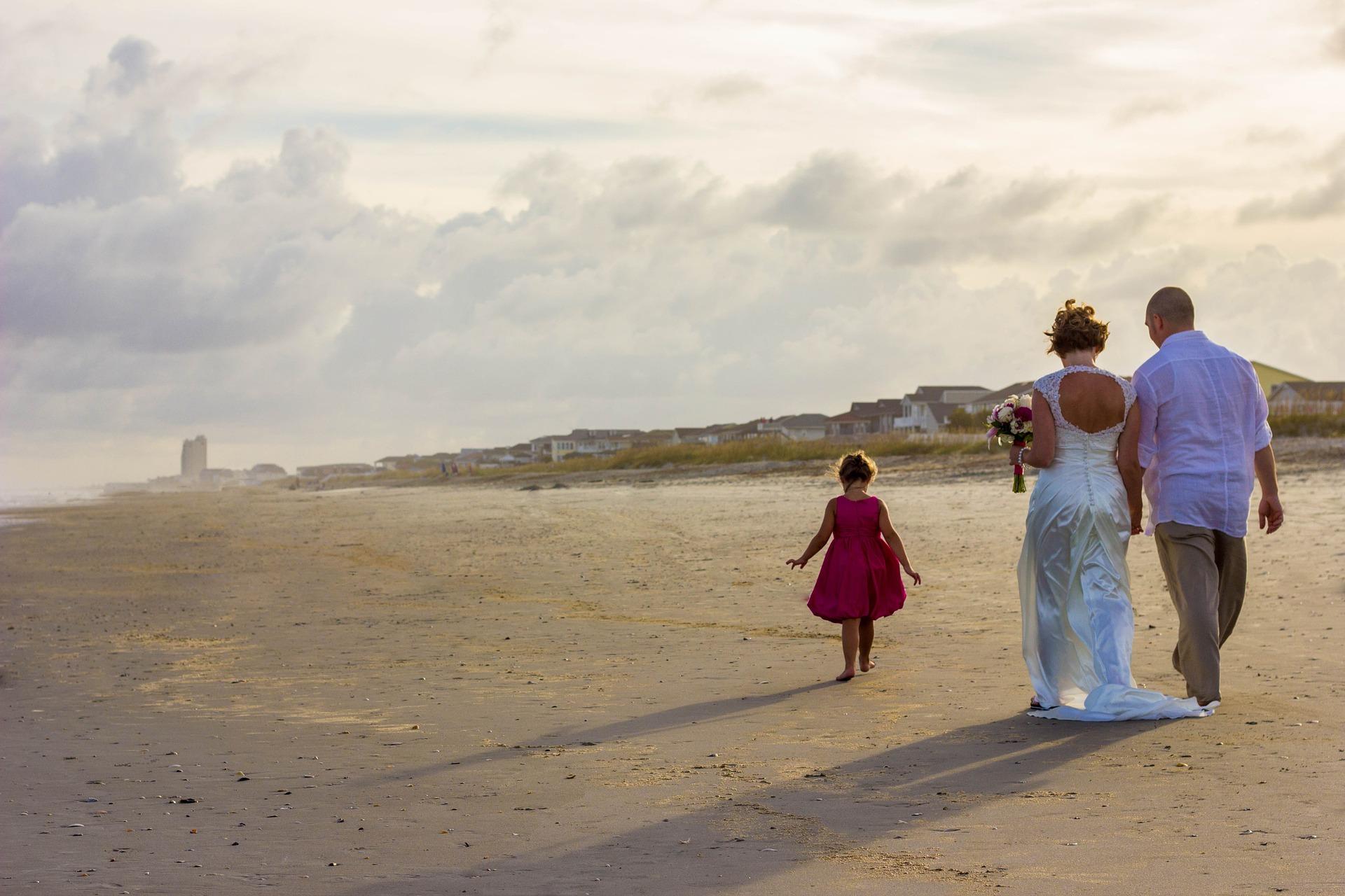 Hochzeitspaar mit Kind am Strand